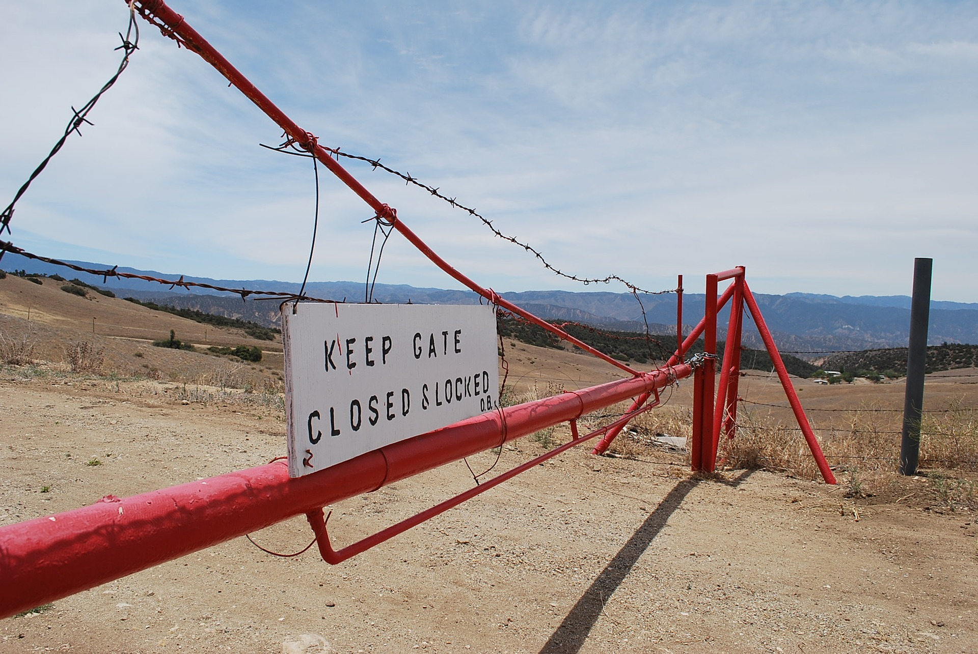 Unwelcome looking gate in arid landscape with barbed wire saying keep gate closed and locked